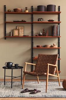 Stylowe wnętrze salonu z designerskim brązowym fotelem, drewnianym regałem, lampą wiszącą, dekoracją dywanową, ramkami na zdjęcia i eleganckimi dodatkami osobistymi w nowoczesnym stylu retro.
