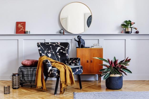 Stylowe wnętrze salonu z designerskimi fotelami, drewnianą komodą vintage, okrągłym lustrem, półką, roślinami, stolikiem kawowym, dekoracją, latarnią, szarą ścianą i osobistymi dodatkami w wystroju domu.