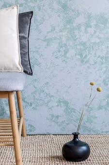 Stylowe wnętrze salonu z designerskimi szarymi poduszkami fotela i eleganckimi dodatkami osobistymi
