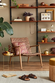 Stylowe wnętrze salonu z rattanowym fotelem, drewnianym regałem, roślinami, pufą, ramą na obraz, dywanem, dekoracją i eleganckimi dodatkami w wystroju domu. szablon.