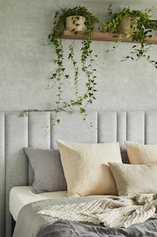 Stylowe wnętrze sypialni w nowoczesnym apartamencie z łóżkiem, przydomowym ogrodem, białą pościelą, poduszkami i kocem. słoneczna przestrzeń z szarymi ścianami. detale. szablon