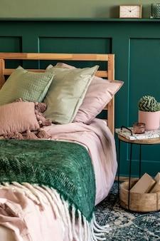 Stylowe wnętrze sypialni z designerskim stolikiem kawowym, rośliną, książką, półką i eleganckimi akcesoriami osobistymi. piękna pościel, koc i poduszka. nowoczesna inscenizacja domowa. panele ścienne.