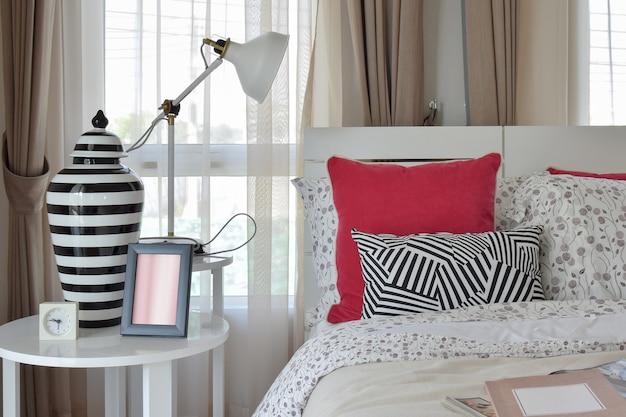 Stylowe wnętrze sypialni z poduszkami w kwiatki i dekoracyjną lampą stołową