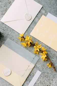 Stylowe zaproszenia ślubne na szarym kamiennym tle zestaw nadruków ślubnych w modnych żółtych odcieniach