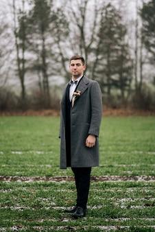 Stylowe zdjęcie ślubne stajennych. piękny elegancki pan młody na zewnątrz w dniu ślubu. zimowe wesele