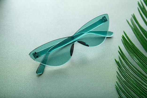Stylowe zielone okulary przeciwsłoneczne. jasne letnie okulary przeciwsłoneczne na zielonym tle z liściem palmowym. modne, luksusowe, modne kolorowe okulary przeciwsłoneczne z optyką.