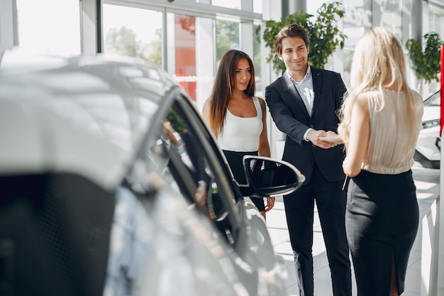 Stylowi i eleganccy ludzie w salonie samochodowym