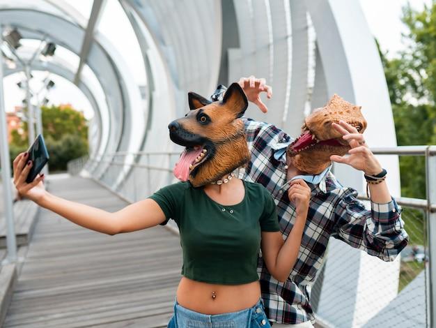 Stylowi ludzie moda para ubrana w maskę t-rex i psa