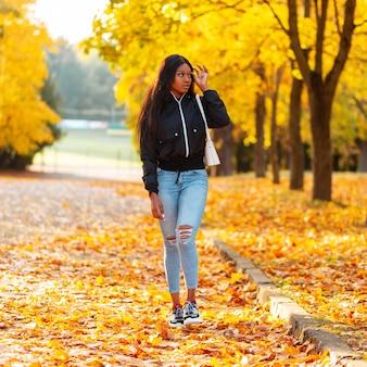Stylowo piękna młoda modelka w swobodnych ubraniach spaceruje po jesiennym parku z jasnymi złotymi liśćmi