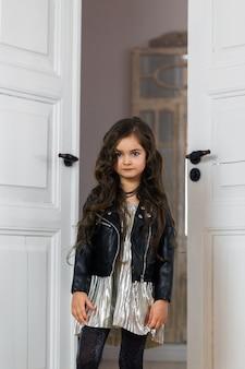 Stylowo ubrana dziewczyna w skórzanej kurtce pozuje we wnętrzu domu