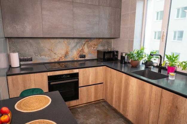 Stylowo wyposażona nowoczesna kuchnia ze sprzętem agd i kamiennymi blatami, wbudowanymi szafkami, zielonymi roślinami doniczkowymi i centralną wyspą na jadalnię