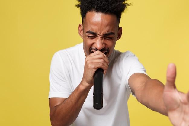 Stylowy afro amerykański mężczyzna śpiewa do mikrofonu