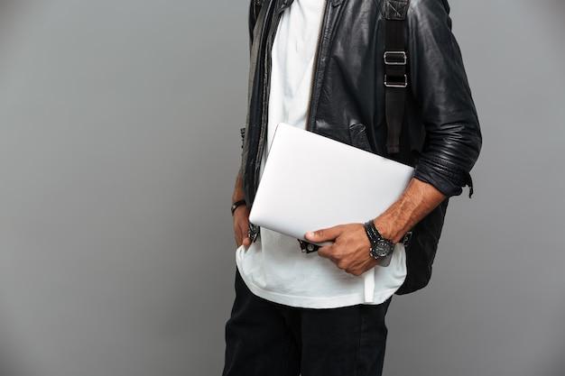Stylowy afrykański mężczyzna w skórzanej kurtce trzyma laptopa