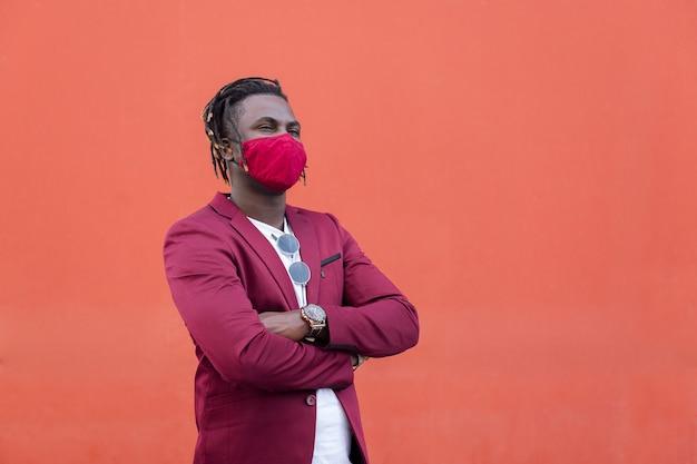 Stylowy afrykański mężczyzna z maską pasującą do jego garnituru