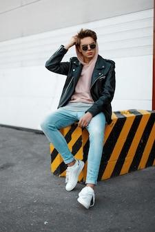 Stylowy amerykański hipster młody mężczyzna w różowej bluzie w modnych okularach przeciwsłonecznych w skórzanej kurtce w dżinsach w białych tenisówkach siedzi na betonowej płycie w paski przed białą bramą. spoko gość