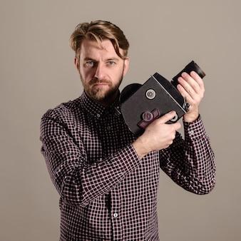 Stylowy, atrakcyjny operator w kraciastej koszuli trzyma w rękach starą kamerę filmową