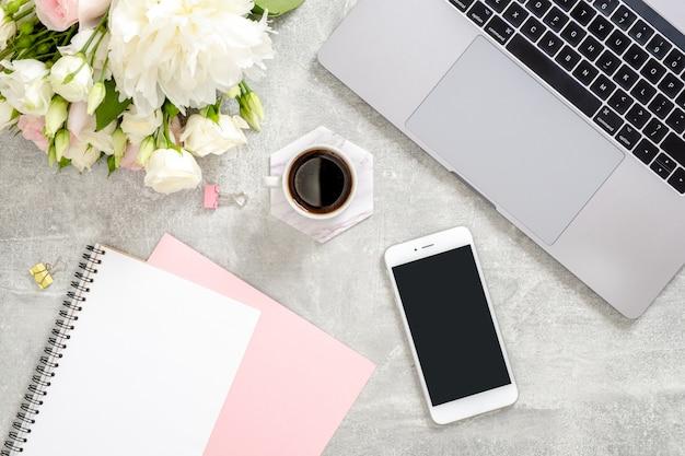 Stylowy betonowy stół biurkowy z laptopem, filiżanką kawy, kwiatami, żeńską ręką piszącą tekst w papierowym notatniku