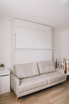 Stylowy, beżowy przytulny pokój z sofą, stołem i łóżeczkiem dziecięcym