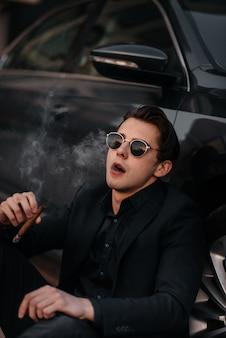 Stylowy biznesmen pali cygara w pobliżu luksusowego samochodu. moda i biznes
