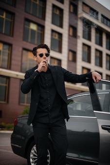 Stylowy biznesmen pali cygara w pobliżu luksusowego samochodu. moda i biznes.