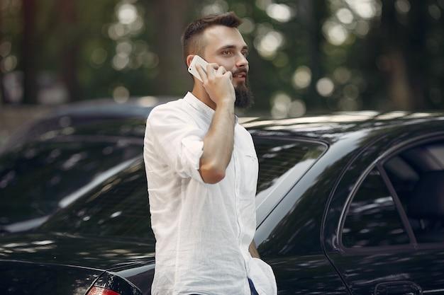 Stylowy biznesmen stojący w pobliżu samochodu i korzystać z telefonu komórkowego