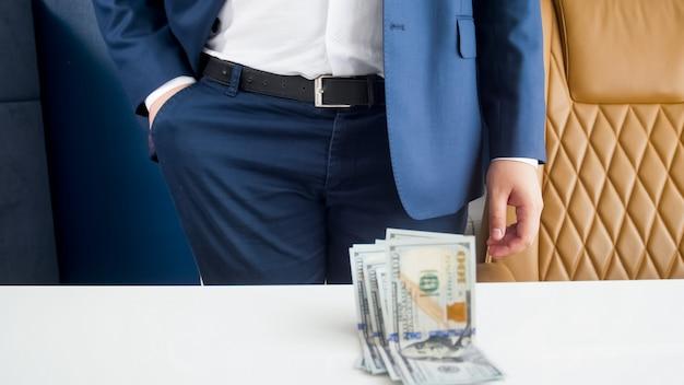 Stylowy bogaty biznesmen w niebieskim garniturze, patrzący na zwitek pieniędzy
