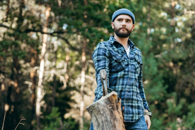 Stylowy brodaty leśniczy rąbał drewno siekierą