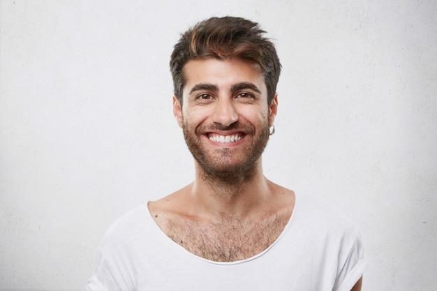 Stylowy brodaty mężczyzna o czarnych oczach, uśmiechniętych i zadowolonych ze spotkania ze swoją dziewczyną. hipster facet z brodą, uśmiechając się i mając wesoły wygląd. pozytywne emocje