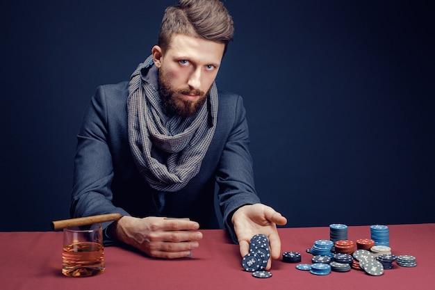 Stylowy brodaty mężczyzna w garniturze i szaliku grający w ciemnym kasynie palący cygaro pić whisky