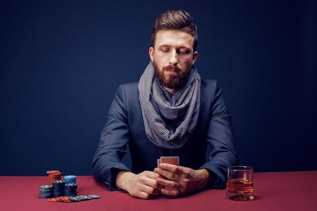 Stylowy brodaty mężczyzna w garniturze i szaliku grającym w ciemnym kasynie