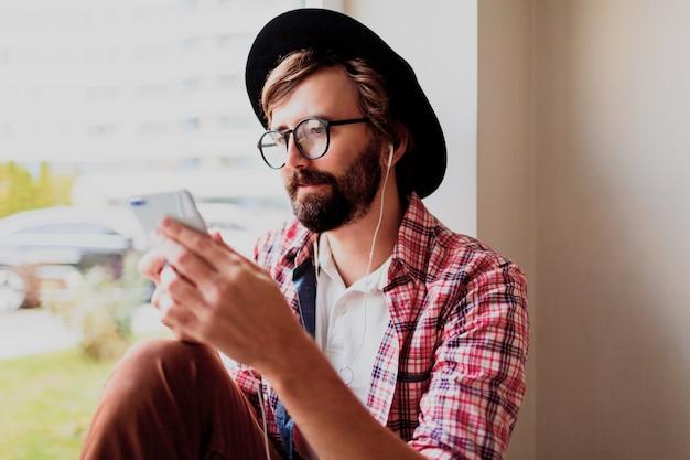 Stylowy brodaty mężczyzna w jasnej kraciastej koszuli instaluje nową aplikację mobilną na smartfonie i słucha muzyki. styl hipster.