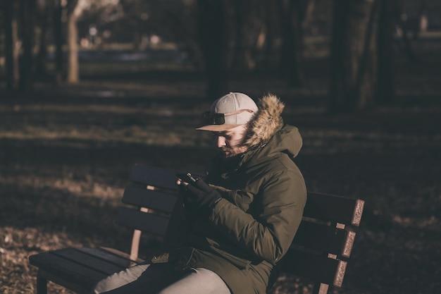 Stylowy brodaty mężczyzna w zimowej kurtce siedzi na ławce ze smartfonem