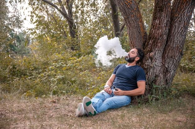 Stylowy brodaty vape man wysadza parę elektronicznego papierosa w lesie