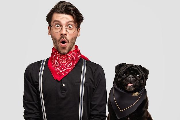 Stylowy brunet mężczyzna ubrany w czerwoną chustkę obok psa