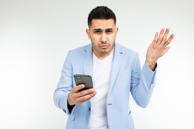 Stylowy brunet w niebieskiej klasycznej kurtce podejrzliwie studiuje informacje w telefonie na białym tle.