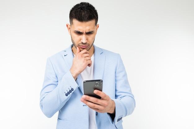 Stylowy brunet w niebieskiej klasycznej kurtce uważnie przygląda się smartfonowi na białym tle.