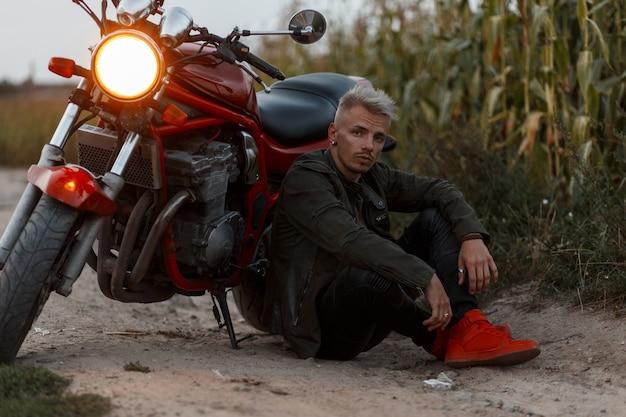 Stylowy, brutalny hipster mężczyzna w modnej wojskowej kurtce z czerwonymi butami siedzi w pobliżu motocykla ze światłem wieczorem na łonie natury