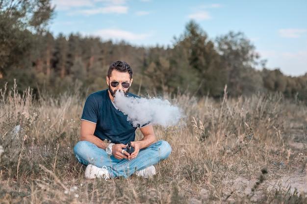 Stylowy brutalny mężczyzna vape wydychający na świeżym powietrzu opary z elektronicznego papierosa