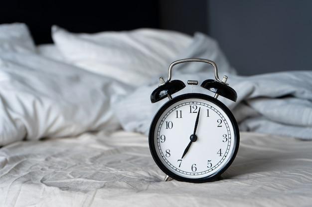 Stylowy budzik z dzwonkiem. wskazówki pokazują 7 godzin. czas się obudzić.