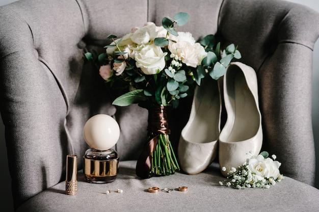 Stylowy bukiet kwiatów panny młodej na fotelu w stylu retro, dodatki ślubne: kwiaty, dziurki na guziki, buty, perfumy, szminki, kolczyki, złote obrączki ślubne na rustykalnym tle. koncepcja wakacji.
