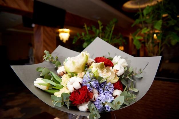 Stylowy bukiet kwiatów w sali restauracyjnej.