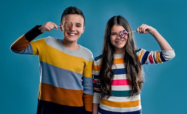 Stylowy chłopak i dziewczyna w kolorowe swetry, zabawy z cukierków lizaków na niebieskim tle.