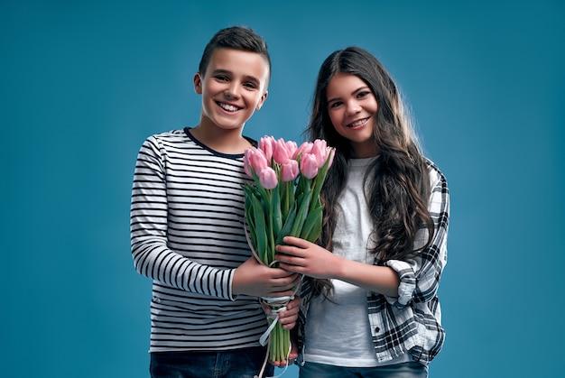 Stylowy chłopak i śliczna dziewczyna z bukietem kwiatów tulipanów na niebieskim tle. dzień matki.