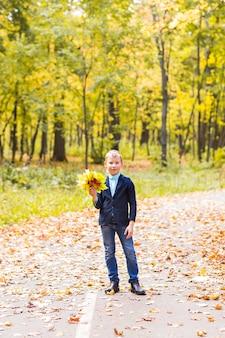 Stylowy chłopak pozuje w jesiennym parku z liśćmi