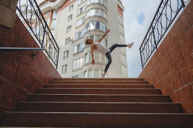 Stylowy chłopak tańczący w mieście, ćwiczący skakanie