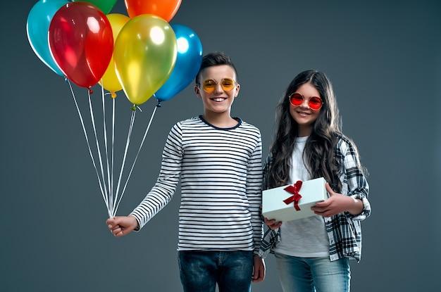 Stylowy chłopak z balonami w okularach i śliczną dziewczyną z pudełkiem na szarym tle.