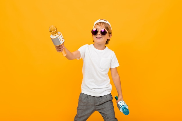 Stylowy chłopak z dwoma mikrofonami śpiewa na jasnej żółtej ścianie