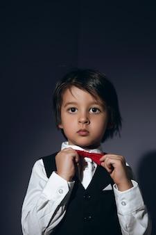 Stylowy chłopiec czteroletni na ścianie w kamizelce i czerwonej muszce