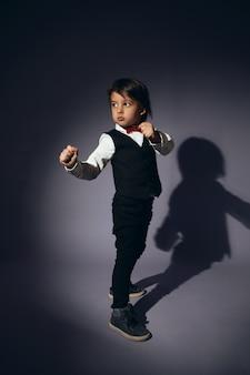 Stylowy chłopiec dziecko na ścianie w kamizelce i czerwonej muszce