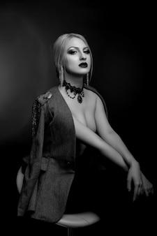Stylowy czarno-biały portret studyjny niesamowitej kobiety z jasnym makijażem noszącej kurtkę na nagim ciele